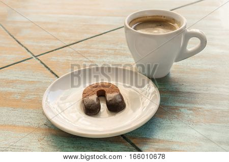 A photo of a cookie in the form of a horseshoe on a plate with a white cup of black coffee, on a wooden board texture with a place for text