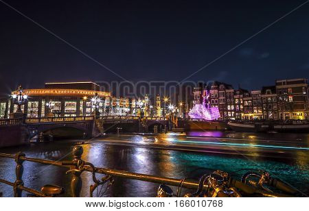 AMSTERDAM NETHERLANDS - JANUARY 12 2017: Cruise boats rush in night canals. Light installations on night canals of Amsterdam within Light Festival. January 12 2017 in Amsterdam - Netherland.