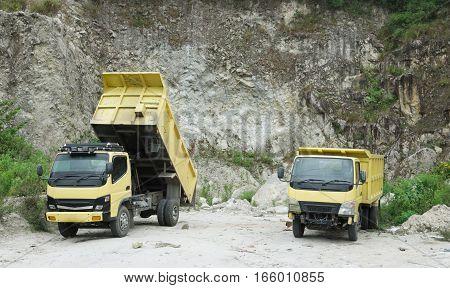 SUMATRA, INDONESIA, 09 DECEMBER 2016 : Two yellow dump trucks in the limestone quarry