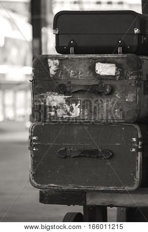 Old vintage suitcases stacked on train railway platform in sepia finish