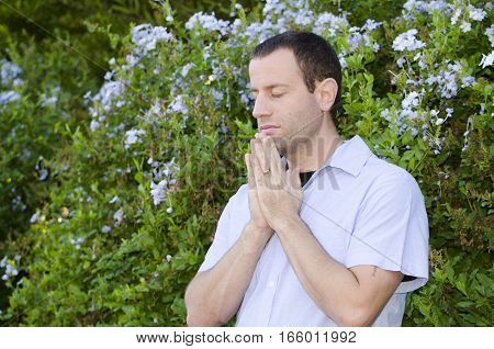 Man praying with hands together and eyes closed.