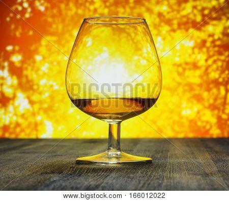 Glass Of Brandy On Evening Sky Background