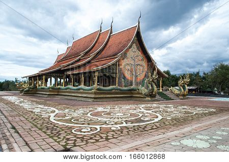 UBON RATCHATHANI, THAILAND-JANUARY 16, 2017 :  Wat Sirindhorn Wararam Phu Prao temple boasts the main hall with nice artwork that is illuminated at dusk. The main artwork is a ceramic tiles wall.