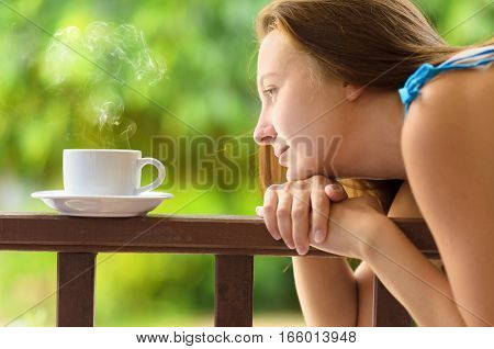 Young woman drinking cofee in a garden. Outdoors portrait.