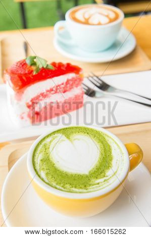 green tea hot milk cup in coffee shop and cake