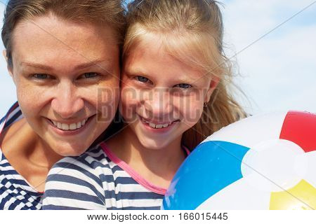 Happy parents and their child playing with a ball at the beach