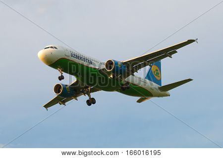 SAINT PETERSBURG, RUSSIA - JULY 03, 2016: Flying the Airbus A320-214 (UK-32020) of the company Uzbekistan Airways in a cloudy sky