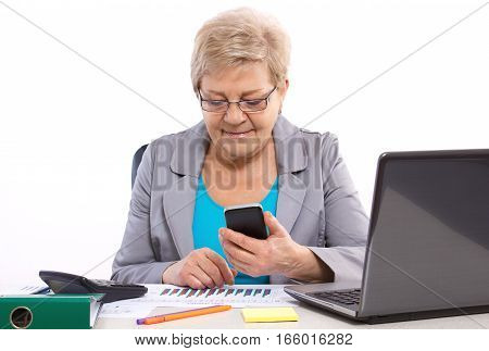 Elderly Business Woman Using Mobile Phone And Working At Her Desk In Office, Business Concept