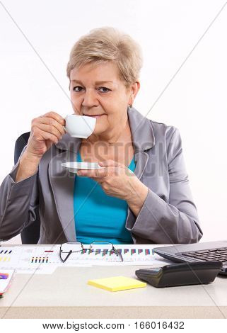 Elderly Business Woman Drinking Tea Or Coffee At Desk In Office, Break At Work