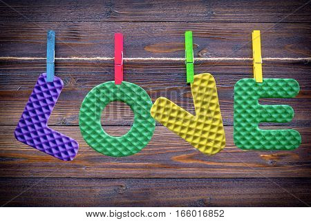 colorful wood cloth peg and colorful love on brown plank background