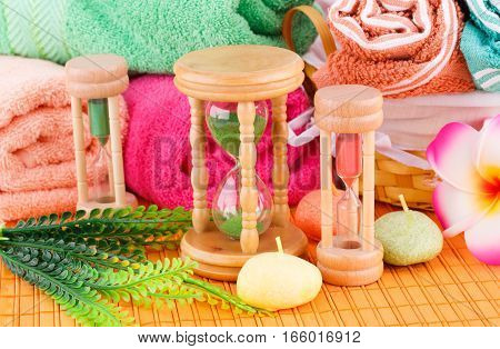 Spa set with colorful towels candles and sandglasses on bamboo background.