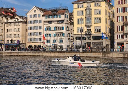 Zurich, Switzerland - 20 April, 2014: two policeman in a motorboat passing along the Limmat river, historical buildings along the river, people on its embankment. The Limmat is a river that commences at the outfall of Lake Zurich.