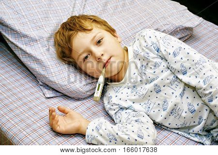 sick boy lying in bed at home