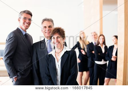 business team posing for a group shot, with managers in front and other employees in the background.