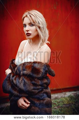 Portrait of the gorgeous sensual young woman in fur coat and lingerie
