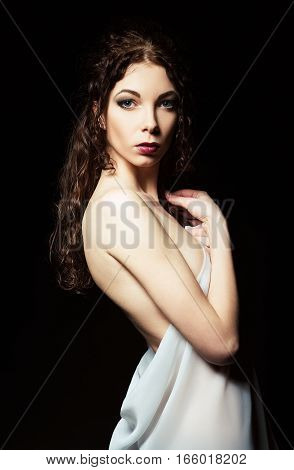Dramatic portrait of sensual young woman among the darkness