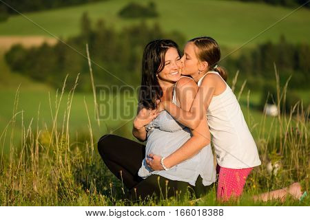 Cute girl child hugging and kissing her pregnant mother