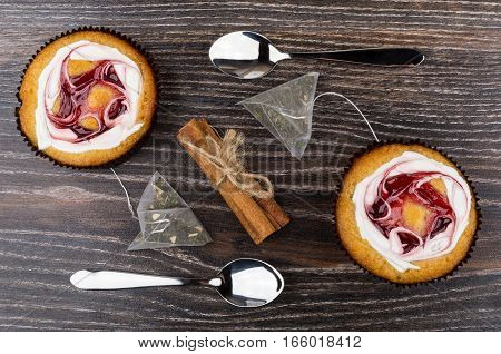 Cakes, Tea Bags Cinnamon Sticks And Teaspoons On Table