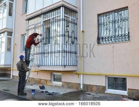 KIEV UKRAINE - January  15  2017: Contractors install window iron security bars