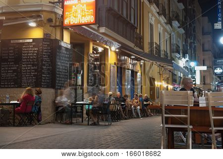 Alicante, Spain - September 8, 2016: Night dining restaurants signs and menus and people sitting out at pavement tables and chairs in back lanes Alicante Spain