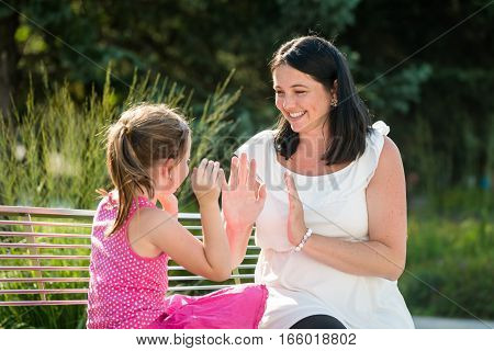 Smiling daughter and mother playing outdoors. Sitting on the bench.
