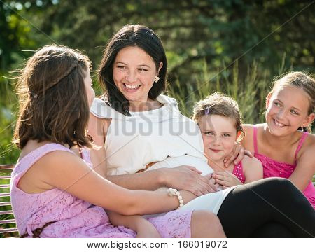Outdoor portrait of a happy young family with pregnant mother.