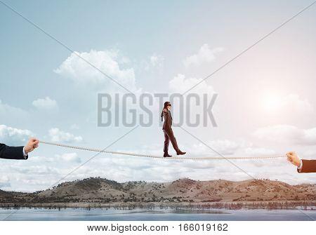 Businessman with blindfolder on eyes walking on rope over gap