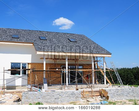 Construction and Renovation of the Rural House with Skylights Eaves Windows Fixing Facade Insulation Plastering and Painting House Facade Wall. Install Plastic Siding Soffits and Eaves Exterior.