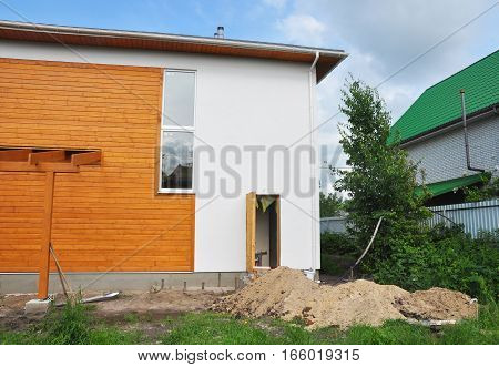 House Construction with New Modern Passive House Facade Wall and Installing water supply system pipe in dirt trench.