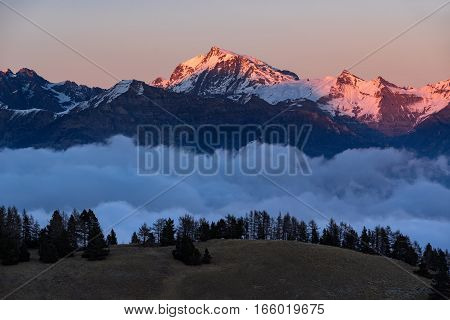 Winter sunset on the Ecrins National Park mountain peaks (Chaillol Queyrel Tourond) raising above the clouds. Champsaur Valley. Hautes Alpes Southern French Alps France