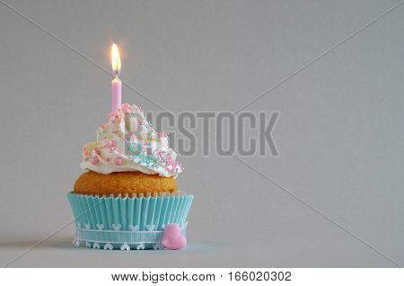 homemade birthday cake with whipping cream, sugar sprinkles, birthday candle and heart