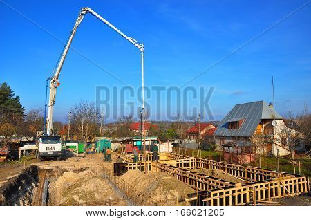 KIEV UKRAINE - JANUARY 23 2017: Contractors making a concrete slab house foundation with car with pump tube. Pouring a concrete slab along the foundation