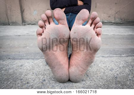 Dirty foot of a man sitting on old concrete floor.