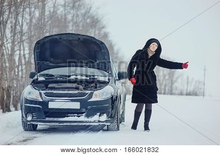Girl on winter road with the car asking for help.