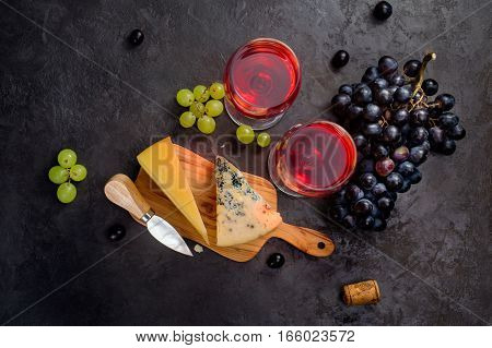 Blue cheese, parmesan, wine and grapes on dark stone background. The view from the top.