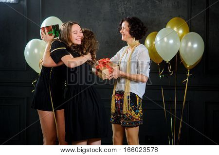 The girl receives congratulations and gifts from girlfriends. The room is decorated with balloons. All are elegantly dressed and joyful.