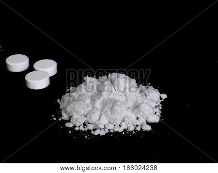 Cocaine drug powder pile and pills on black background