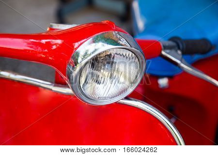 the headlight of red motorcycle close up