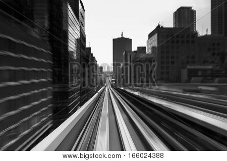 Black and white abstract blur motion train moving in to city downtown