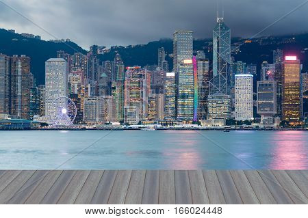 Opening wooden floor Office building over seacoast skyline Hong Kong city night view