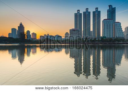 City office building with reflection over the lake during sunrise
