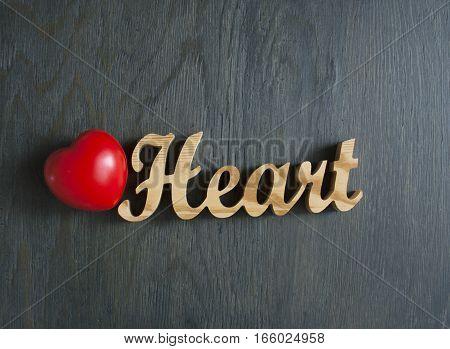 Wooden word - Heart on a dark green background