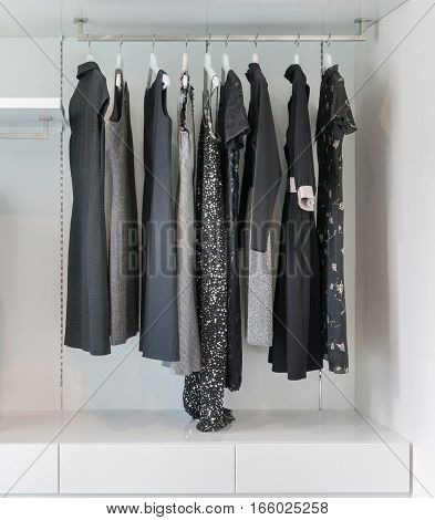 Modern Closet With Row Of Black Dress Hanging In White Wardrobe.
