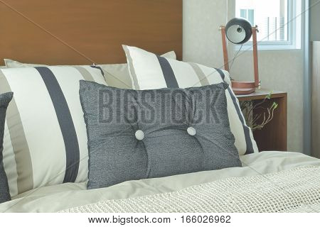 Gray And Brown Strip Pillows Setting On Bed With Brown Headboard