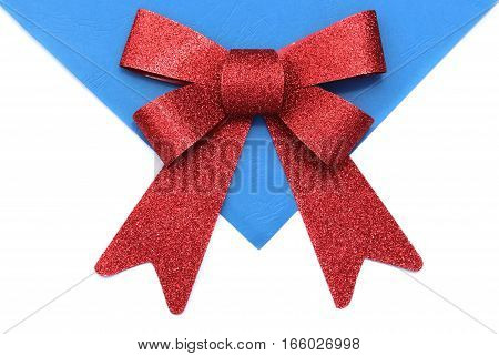 Red bow for presents on white and blue paper background