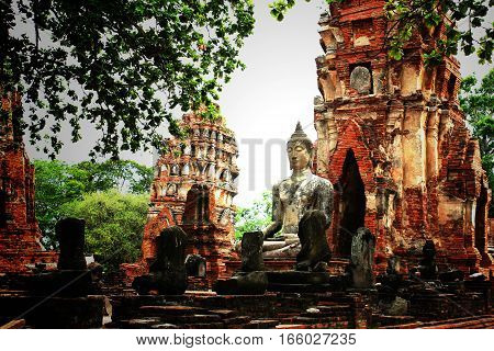 Old Buddha Statue and Old Temple Architecture at Wat Mahathat Ayutthaya Thailand.