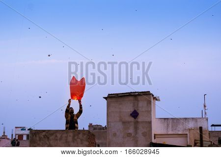 Jaipur, India - 14th Jan 2017: People release a chinese lantern into the air as part of Makar Sankranti or Uttaryan celebration in Rajasthan India. This is a recent trend