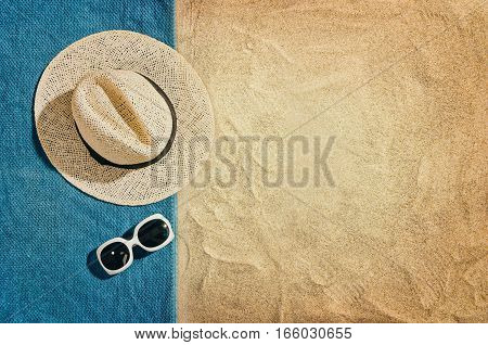 Top view of sandy beach with towel frame and summer accessories. Background with copy space and visible sand texture. Left border made of towel