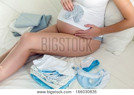 young pregnant girl sitting in white bed with baby clothes
