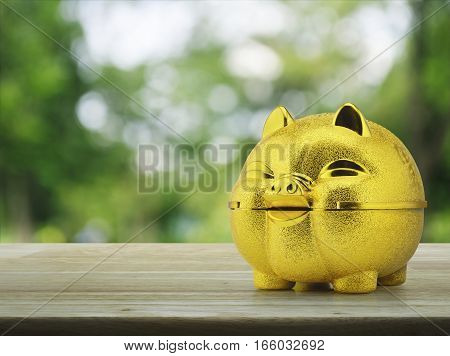 Gold piggy bank on wooden table over blur green tree background Saving money concept